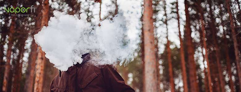 A man vaping and creating huge smoke clouds in the forest.